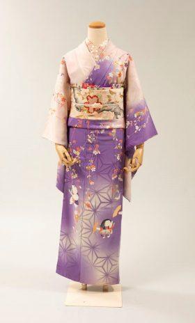 「細雪」雪子の着物 ヒロイン雪子のモデルは妻・松子の妹重子である。桜と童子が描かれた紫の着物に、やはり桜の樹木が描かれた帯、帯揚げ帯留も桜と、桜尽くしのコーディネート。姉妹四人のキャラクターに合わせ、それぞれの着物を田中翼氏がセレクト。 田中翼コレクション/蔵 大橋愛/撮影 『谷崎潤一郎をめぐる人々と着物』(東京美術刊)